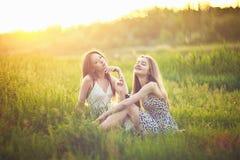 Jeunes filles s'asseyant sur l'herbe dans des rayons et parler du soleil Photos stock
