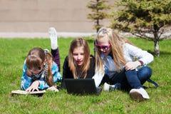 Jeunes filles se trouvant sur une herbe Photos stock