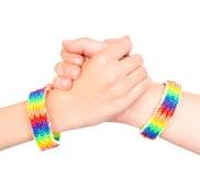 Jeunes filles serrant la main à un bracelet modelé comme drapeau d'arc-en-ciel D'isolement sur le fond blanc Photos libres de droits