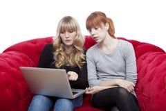 Jeunes filles sur le sofa rouge affichant sur l'ordinateur portatif Photos libres de droits