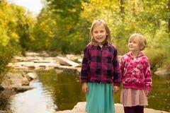 Jeunes filles - tenir des mains par la rivière Photographie stock libre de droits