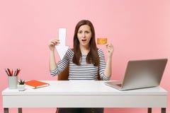 Jeunes flèche de chute de valeur de maintien de femme, carte de crédit bouleversées se reposer et travailler au bureau blanc avec images libres de droits