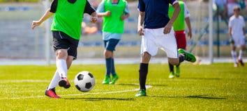 Jeunes footballeurs fonctionnant après la boule sur le lancement photographie stock libre de droits