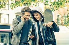 Jeunes frères de meilleurs amis de hippie ayant l'amusement avec le smartphone Images stock