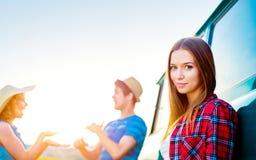 Jeunes frieds avec l'extérieur campervan en nature ensoleillée verte Photos libres de droits