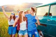 Jeunes frieds avec la nature campervan et verte et le ciel bleu Images libres de droits