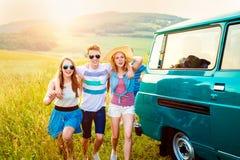 Jeunes frieds avec la nature campervan et verte et le ciel bleu Photos stock