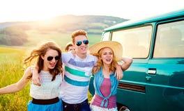 Jeunes frieds avec la nature campervan et verte et le ciel bleu Photo stock
