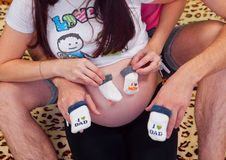 Jeunes futurs parents avec des vêtements de chlidrens à Photos stock