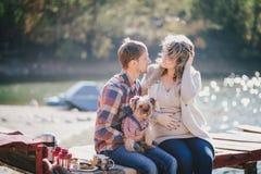 Jeunes futurs parents et leur chien dans un costume drôle se reposant sur un pont en bois et ayant le pique-nique près du lac Photographie stock libre de droits