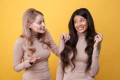 Jeunes gais deux dames se tenant au-dessus du fond jaune Image stock
