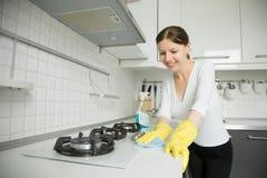 Jeunes gants jaunes en caoutchouc de port de sourire de femme nettoyant le St Photographie stock