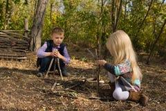 Jeunes garçon créatif et fille jouant avec des branches Photographie stock libre de droits