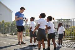 Jeunes garçons dans un terrain de jeu d'école avec le professeur tenant la boule images libres de droits