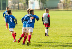 Jeunes garçons du football huging pendant le match de football Image stock
