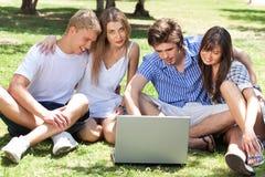 Jeunes garçons et étudiantes à l'aide de l'ordinateur portatif Photographie stock libre de droits