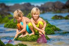 Jeunes garçons heureux jouant à la plage des vacances d'été Photo libre de droits