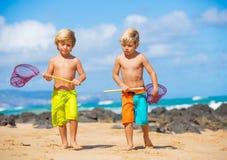 Jeunes garçons heureux jouant à la plage des vacances d'été Photographie stock libre de droits