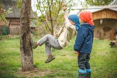 Jeunes garçons jouant sur l'arrière-cour - corde s'élevante près de l'arbre Photo libre de droits