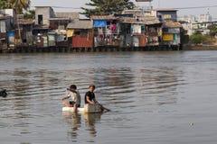 Jeunes garçons pêchant en rivière polluée Images stock