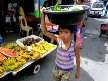 Jeunes garçons sur un marché du cainta, rizal, Philippines vendant des fruits et légumes image libre de droits
