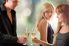 Jeunes glaces de fixation de couples avec le champagne et la femme regardant Images stock