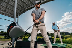 Jeunes golfeurs avec des clubs jouant le golf ensemble Images libres de droits