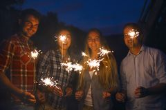 Jeunes happpy avec des cierges magiques ayant l'amusement Photos libres de droits