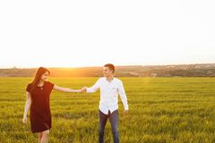 Jeunes, heureux, affectueux couples, au coucher du soleil, se tenant dans un domaine vert, contre le ciel tenant des mains, et s' Photos stock