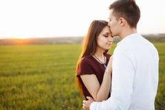 Jeunes, heureux, affectueux couples, au coucher du soleil, se tenant dans un domaine vert, contre le ciel, dans les bras, et s'am Image libre de droits