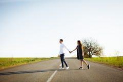 Jeunes, heureux, affectueux couples se tenant sur la route tenant des mains et regardant l'un l'autre, la publicité et insérant l Image libre de droits