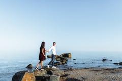 Jeunes, heureux, affectueux couples se tenant sur les roches en mer, dans les bras, et regardant l'un l'autre, la publicité et in Image libre de droits