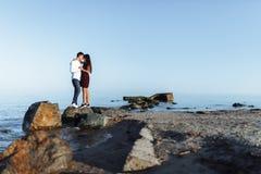 Jeunes, heureux, affectueux couples se tenant sur les roches en mer, dans les bras, et regardant l'un l'autre, la publicité et in Photos libres de droits