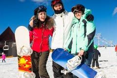 Jeunes heureux dans des costumes de ski se tenant avec des surfs des neiges Image stock