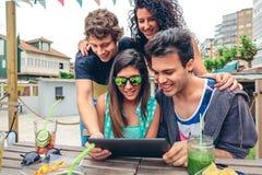 Jeunes heureux regardant le comprimé au-dessus de la table Photographie stock