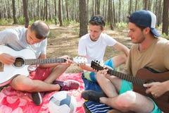 Jeunes hippies détendant dans la forêt dehors Photographie stock