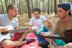 Jeunes hippies détendant dans la forêt dehors Photo stock