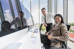 Jeunes homme d'affaires asiatique et femme d'affaires s'asseyant devant le GR photographie stock libre de droits