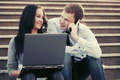 Jeunes homme et femme d'affaires avec l'ordinateur portable Photographie stock libre de droits