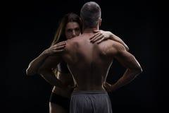 Jeunes homme et femme musculaires adultes Couples sexy sur le fond noir Images libres de droits