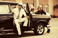 Jeunes homme et femmes heureux de mode en la voiture de vintage Photographie stock
