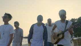 Jeunes hommes adultes asiatiques marchant sur la chanson de chant de plage et jouer la guitare banque de vidéos