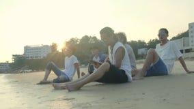 Jeunes hommes adultes asiatiques s'asseyant sur le chant de détente de plage jouant la guitare banque de vidéos