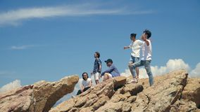 Jeunes hommes adultes asiatiques se tenant sur des roches à côté de la mer banque de vidéos