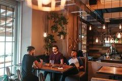 Jeunes hommes Arabes accrochant en café de grenier Le groupe de personnes de métis parlant dans le salon barrent et ayant des boi Images stock