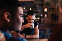 Jeunes hommes Arabes heureux accrochant en café de grenier Amis parlant dans la barre de salon par le thé potable de fenêtre Photographie stock libre de droits