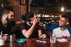 Jeunes hommes arabes heureux accrochant en café de grenier Groupe de personnes de métis ayant l'amusement dans la barre de salon Photo stock