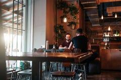 Jeunes hommes Arabes heureux accrochant en café de grenier Groupe de personnes de métis parlant dans la barre de salon Photo libre de droits