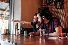 Jeunes hommes Arabes parlant dans la barre de salon Les amis multiraciaux regardent la fenêtre et se dirigent dehors Photographie stock