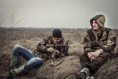 Jeunes hommes avec l'expression sereine et paisible dans le camouflage ayant le repos dans le domaine rural détendant sur l'herbe Images stock